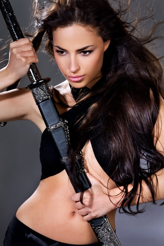 beautiful long hair brunette holding katana weapon, studio shot